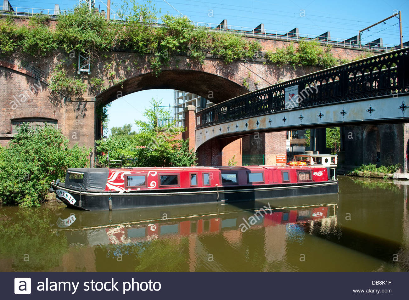 Longboat on Bridgewater canal near the railway viaduct, Manchester, UK - Stock Image