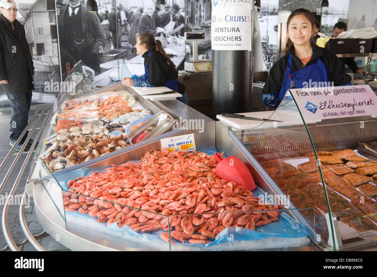 Bergen Norway Europe Chinese student earning pocket money working indoor market stall  world famous Fish Market - Stock Image