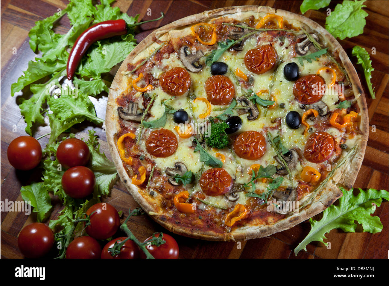 Pizza surrounded with vegetables - Stock Image