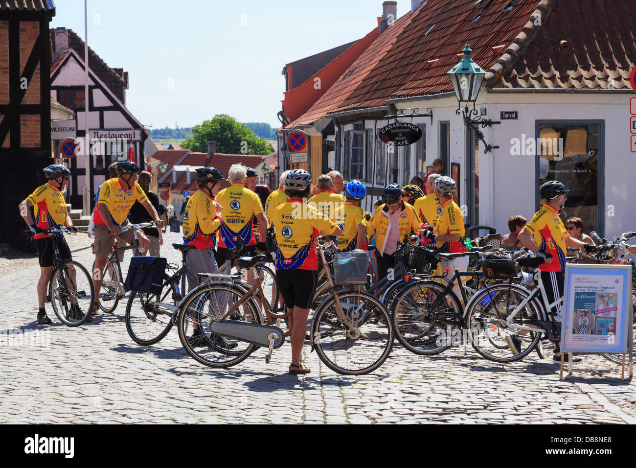 Cycling club of senior cyclists with bicycles on cobbled street in summer in old town of Ebeltoft, Central Jutland, - Stock Image