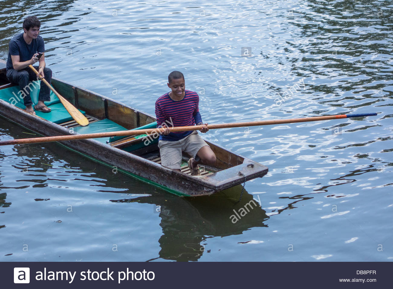 Smiling and laughing punter returns the pole to a group of inexperienced punters on the River Cam - Stock Image