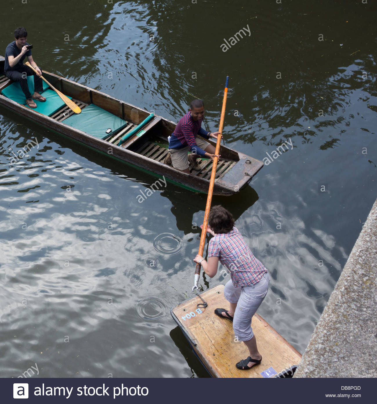Punting in Cambridge - Punters return the pole to a group of inexperienced punters on the River Cam - Stock Image