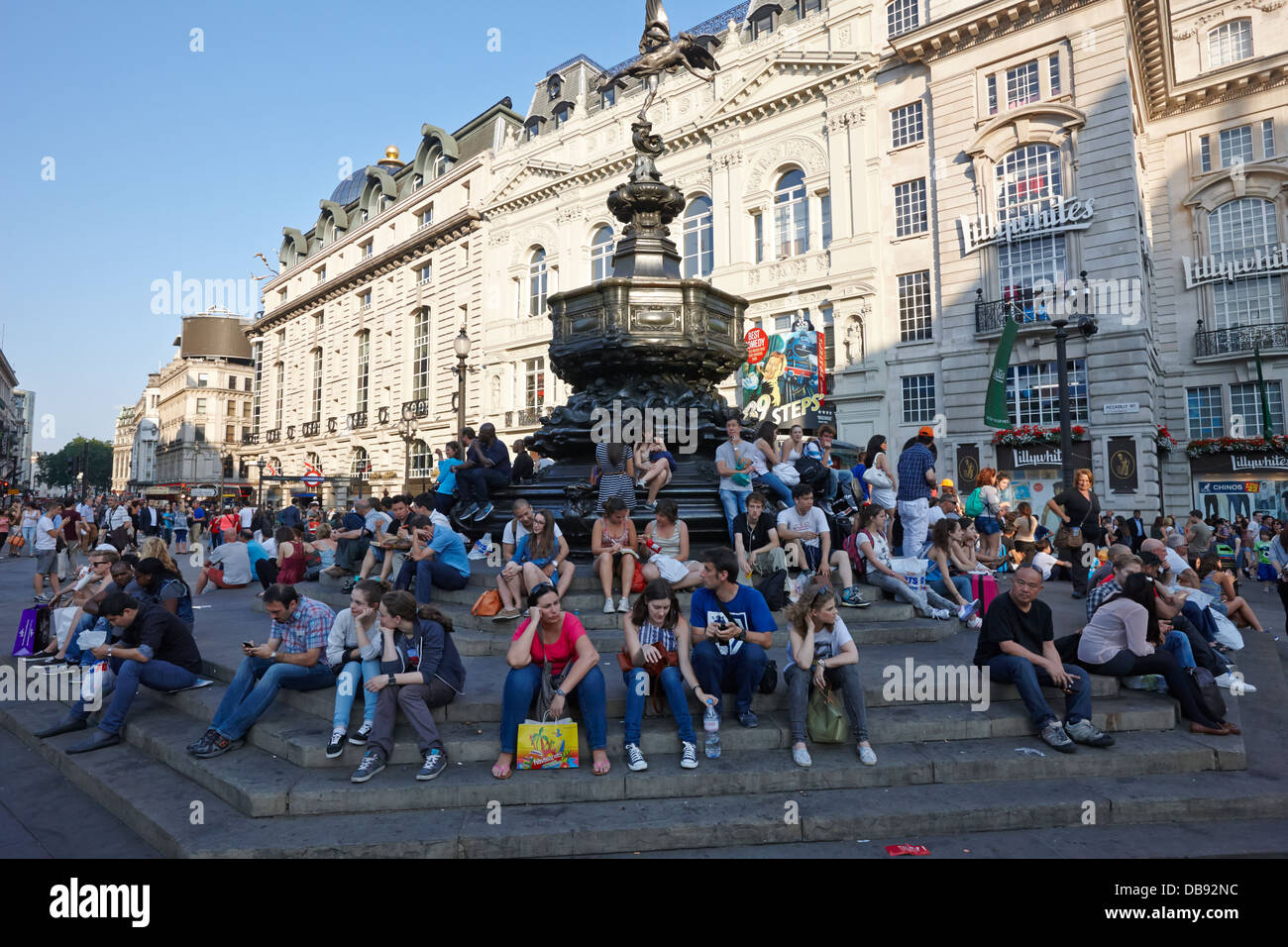 tourists and visitors sit on the steps of the eros statue in picadilly circus London England UK - Stock Image