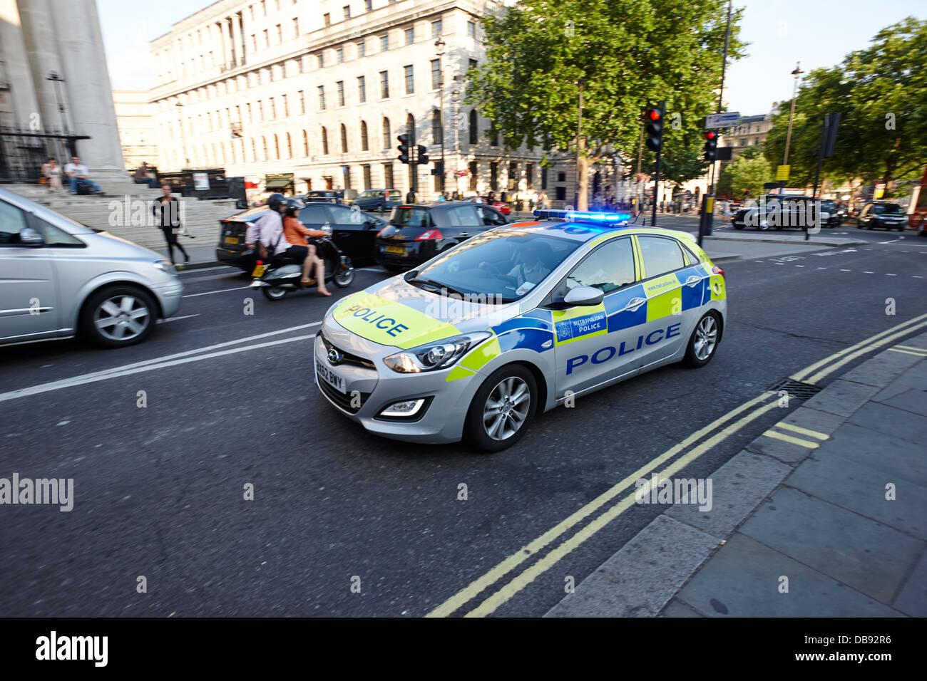 metropolitan police patrol car speeding through streets with blue lights on London England UK Stock Photo
