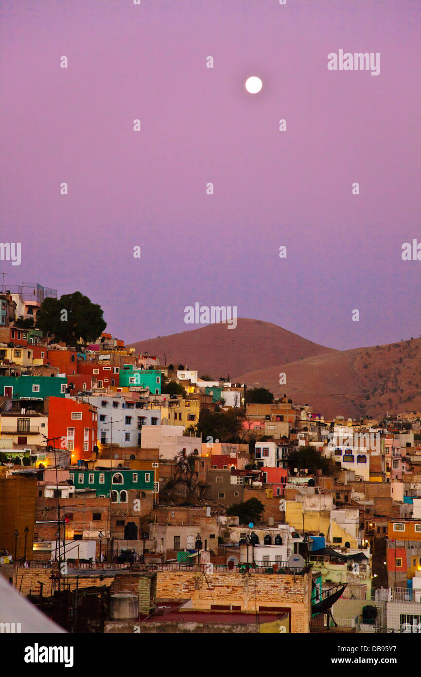The full MOON rises over the colorful houses on the hillside of the cultural city of GUANAJUATO in central MEXICO - Stock Image