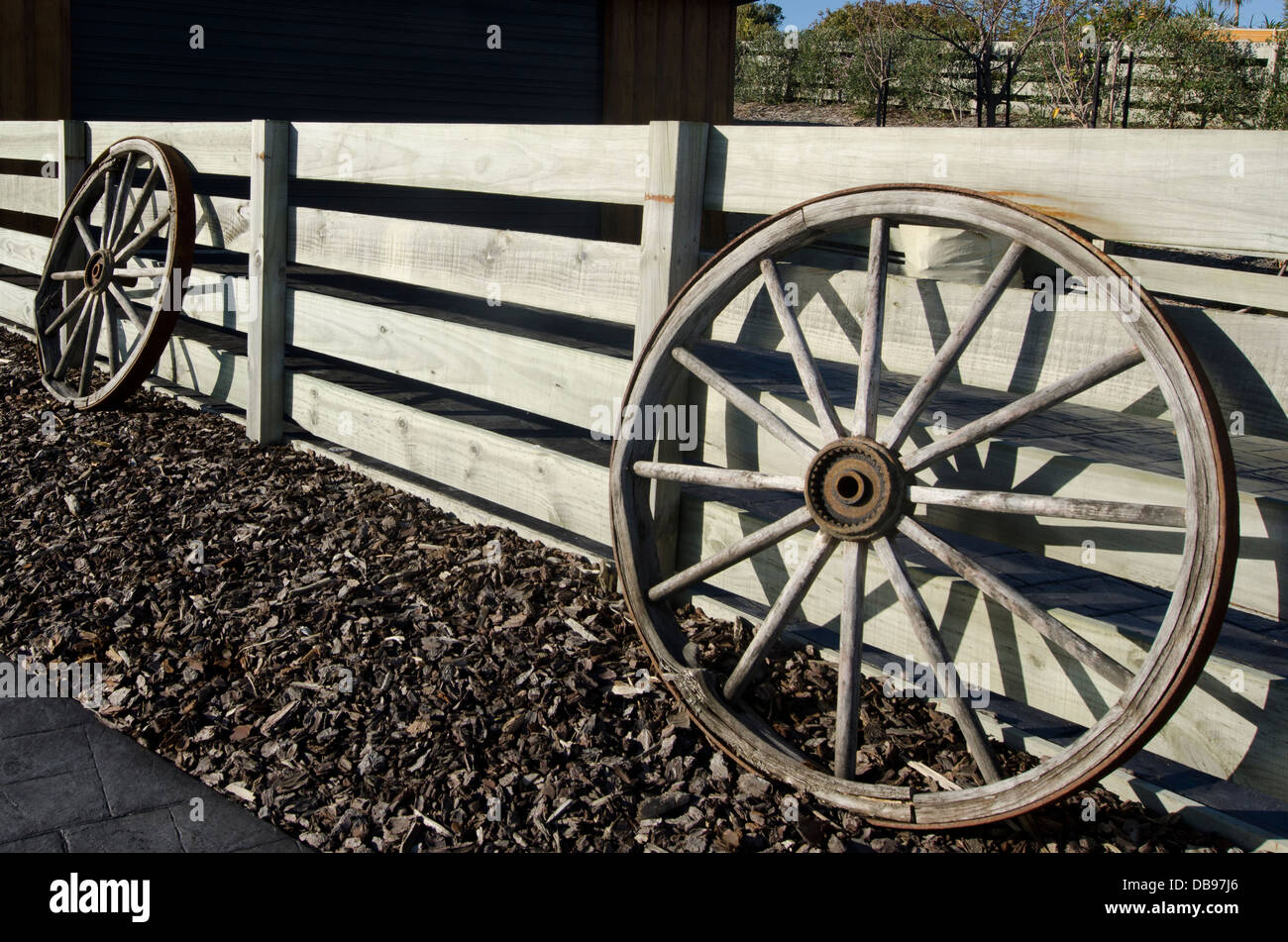 Vintage carriage wheels on lean on a farm fence. - Stock Image