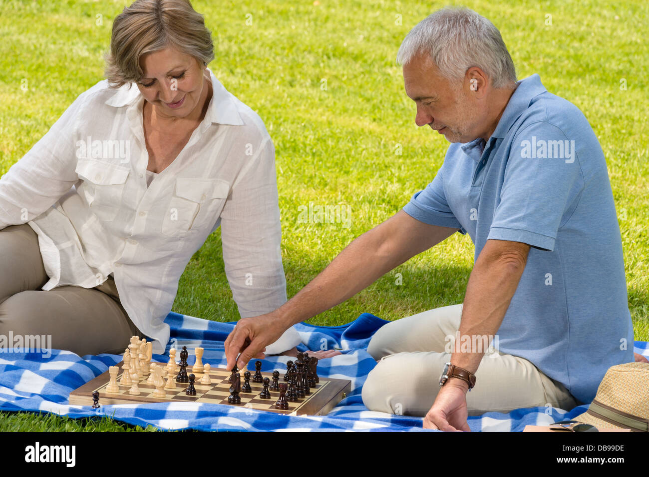 Retired senior couple playing chess in park sitting blanket grass - Stock Image