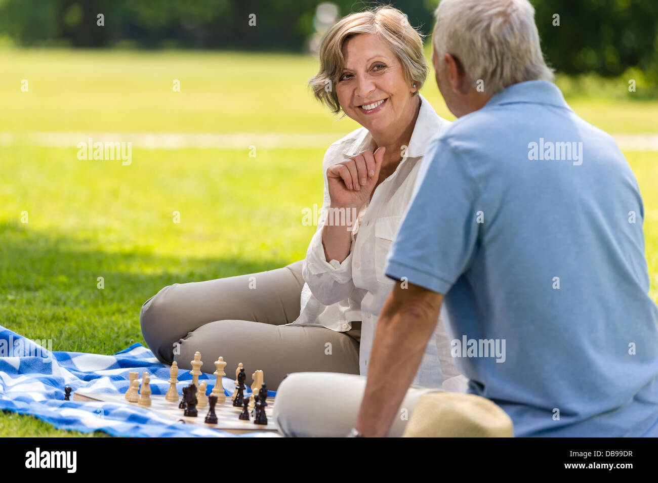 Senior wife and husband playing chess on blanket summer park - Stock Image