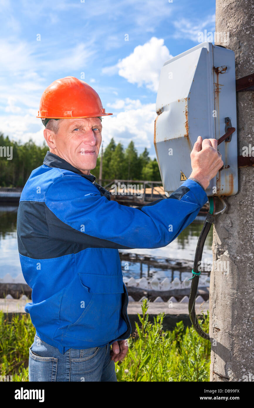 Caucasian senior worker man turning the power switch in an industrial plant - Stock Image