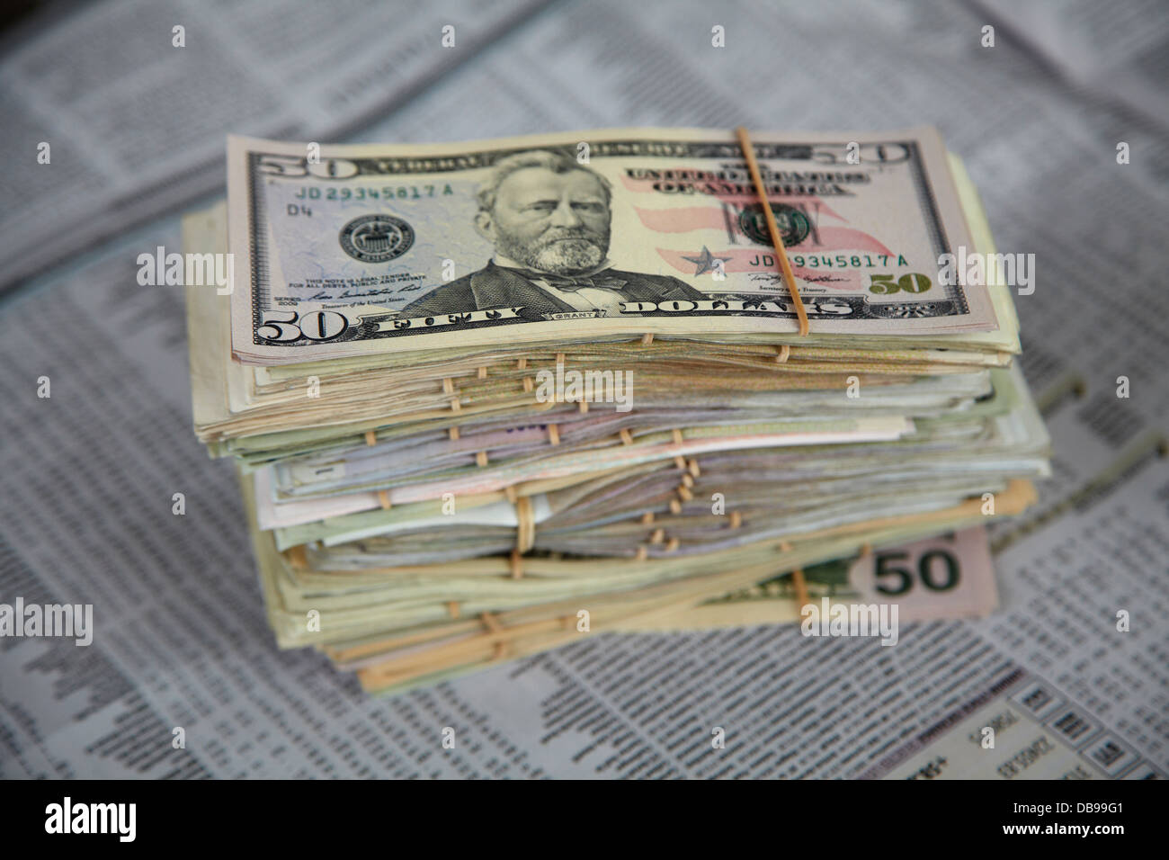 US dollars and financial pages in newspaper - Stock Image