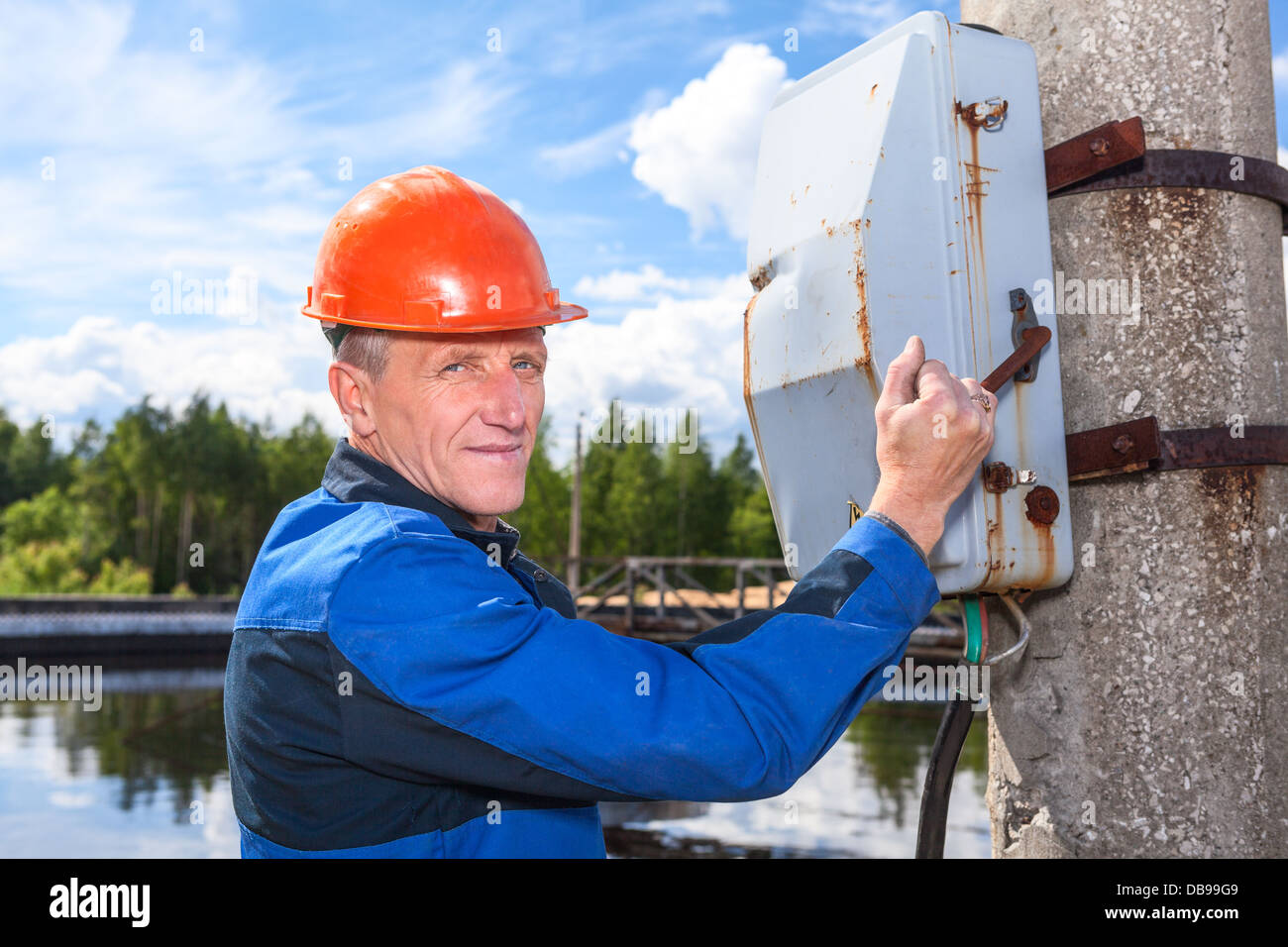 Caucasian senior worker man turning the power switch - Stock Image