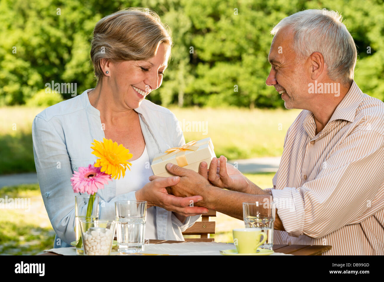 Retired Caucasian couple smiling and holding gift outdoors - Stock Image