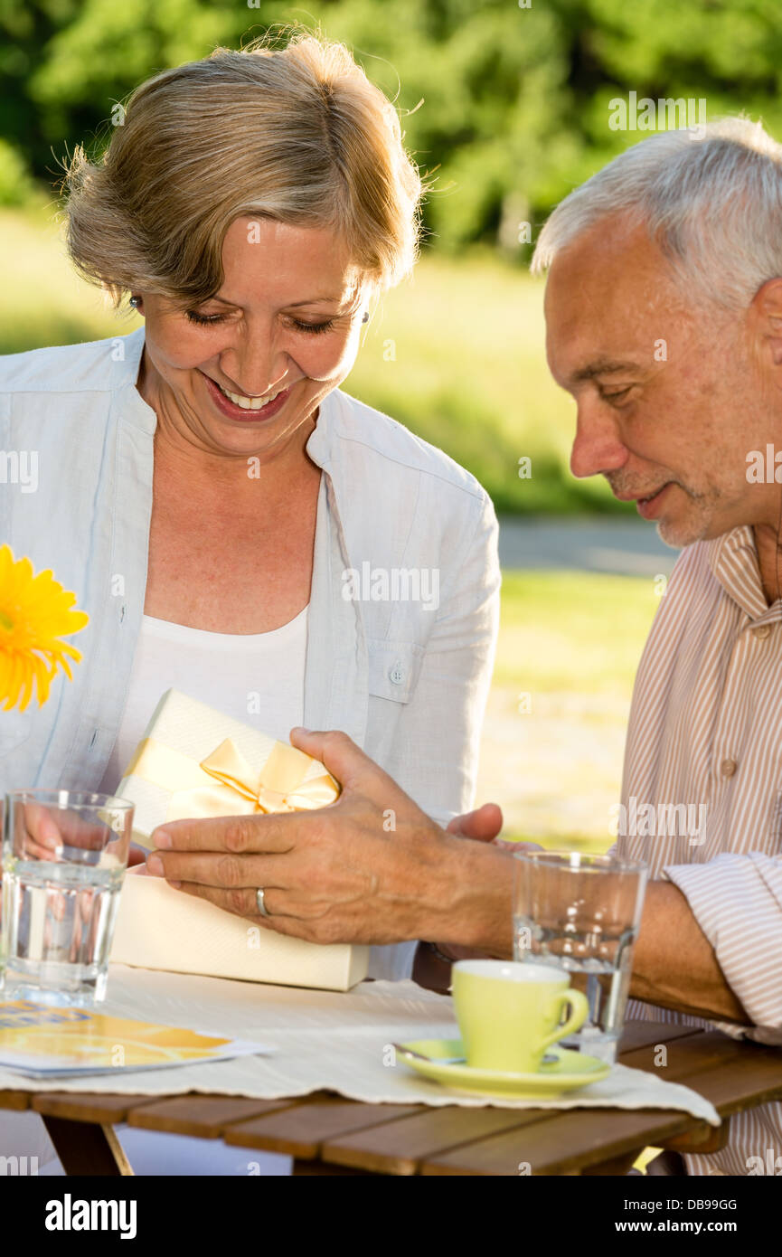Elderly married couple opening present together - Stock Image