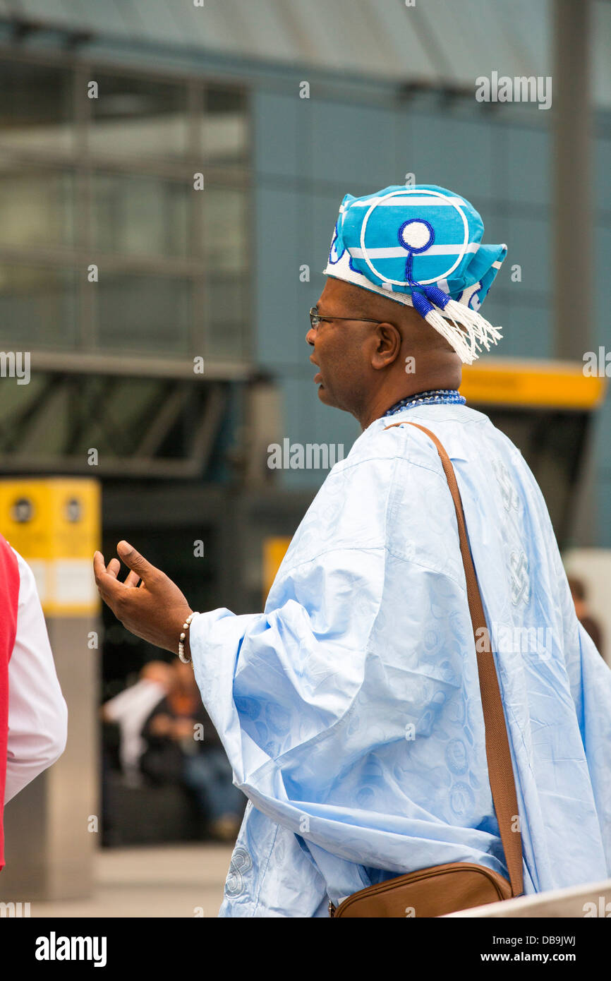 An African gentleman in traditionl African dress at Heathrow Airport, London, UK. - Stock Image