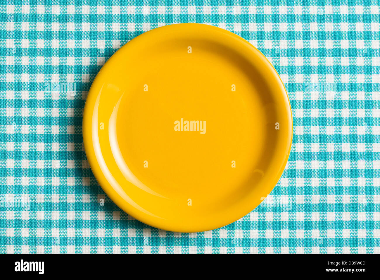 the empty plate on checkered tablecloth - Stock Image