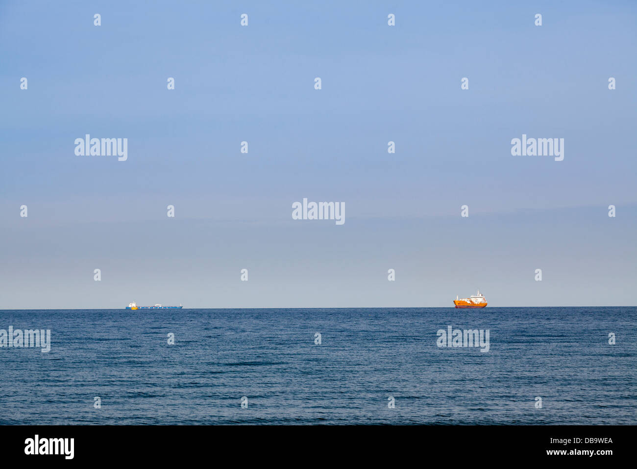 Container ships on horizon at sea. - Stock Image