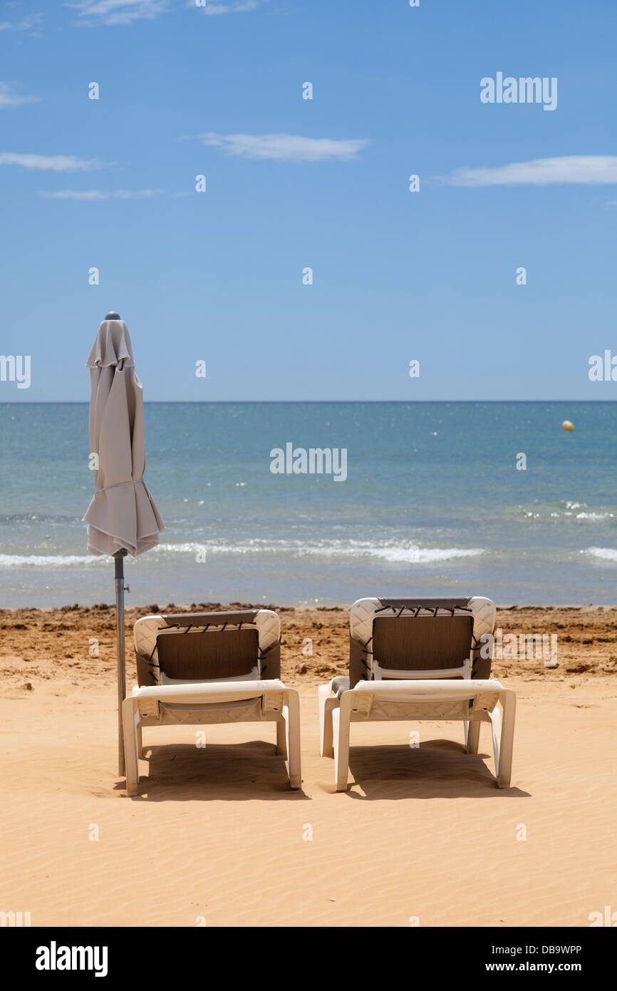 two unoccupied sun loungers on beach with furled umbrella and sea - Stock Image