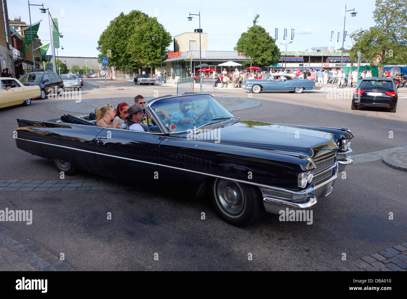 Rockabilly style people riding in a classic car on the road in Varberg town, Sweden - Stock Image