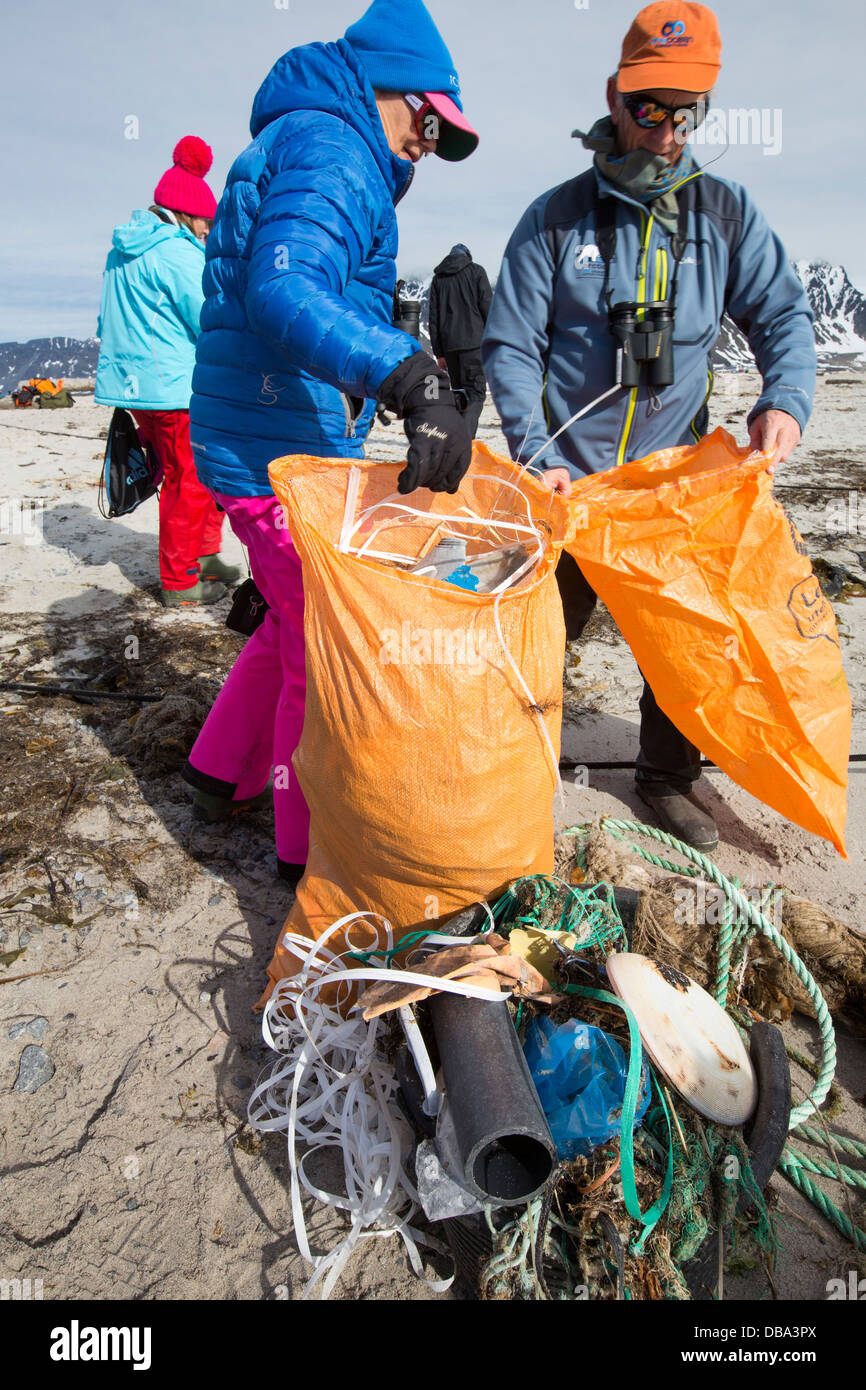 Tourists collect plastic rubbish on a remote beach in Northern Svalbard, only about 600 miles from the North Pole. - Stock Image