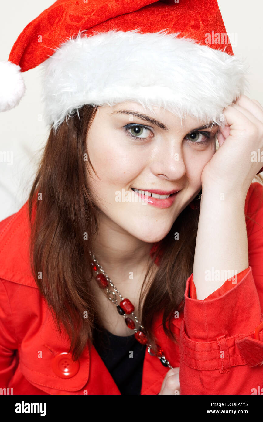 A teenage girl with a big smile wearing a santa hat - Stock Image