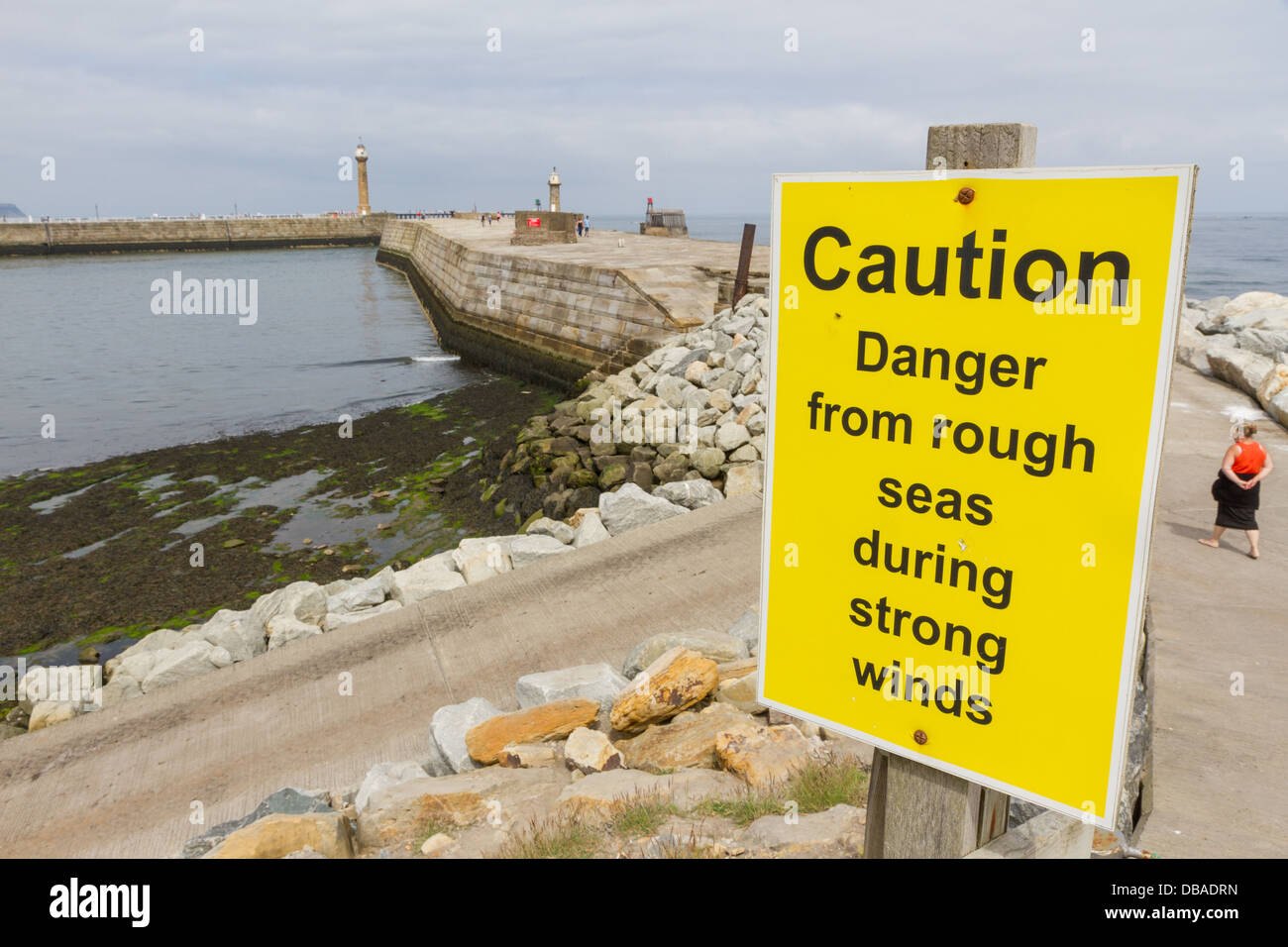 Caution sign about rough seas at Whitby Harbour Wall, North Yorkshire. - Stock Image