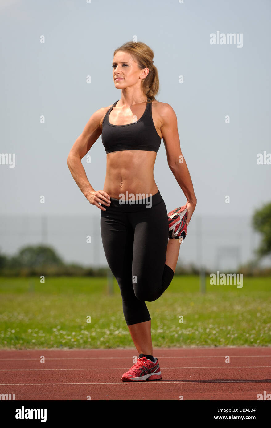 Female stretching legs during fitness program prior to running - Stock Image