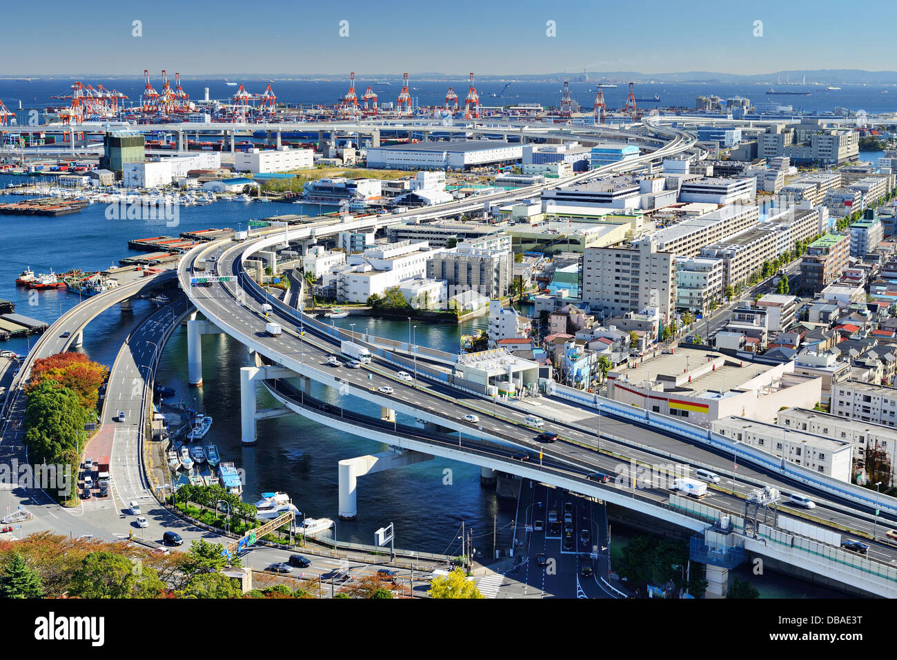 Metropolitan Expressway passes ports in the distance in Yokohama, Japan, the second largest city in the country. - Stock Image