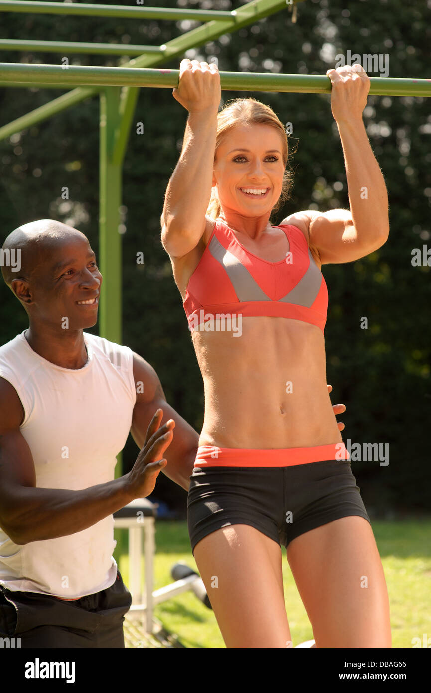 Female with personal trainer during outdoor fitness program - Stock Image