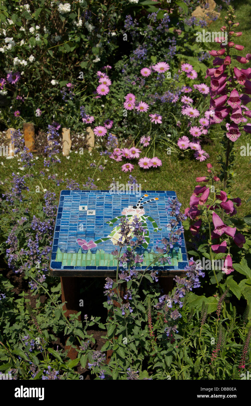 Decorative tile and insect friendly planting in Bugs in Boots garden at RHS Hampton Court Palace Flower Show 2013, - Stock Image
