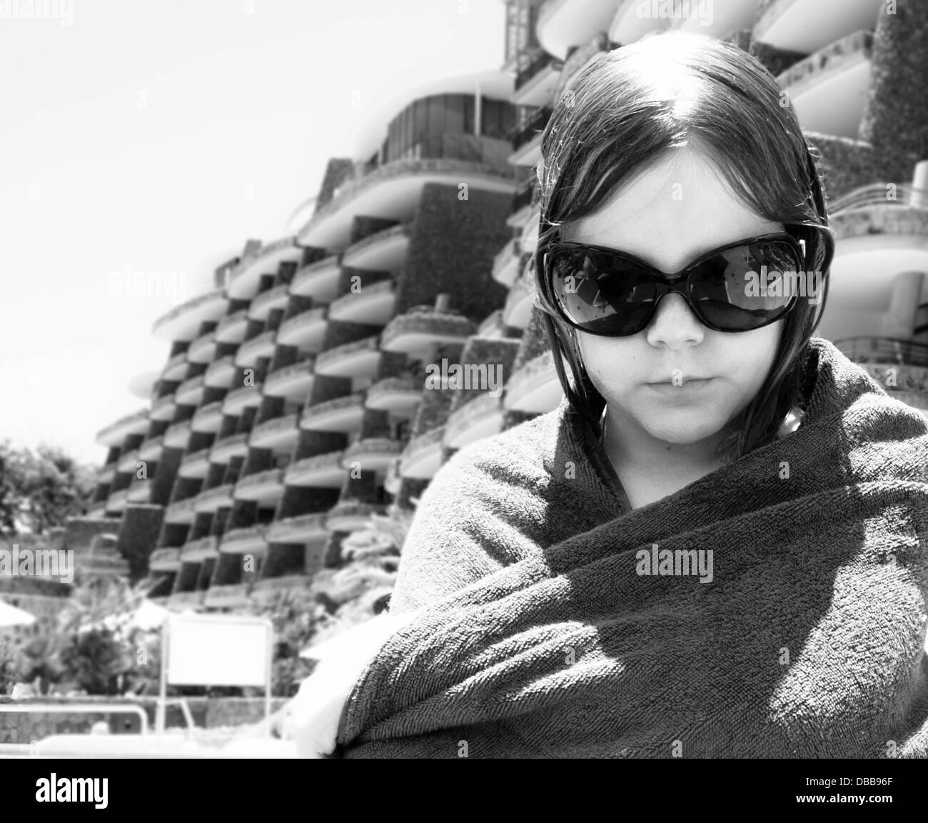 pre-teen girl, big sun glasses looking down. wet hair. towel wrapped around her shoulders. black and white. old - Stock Image