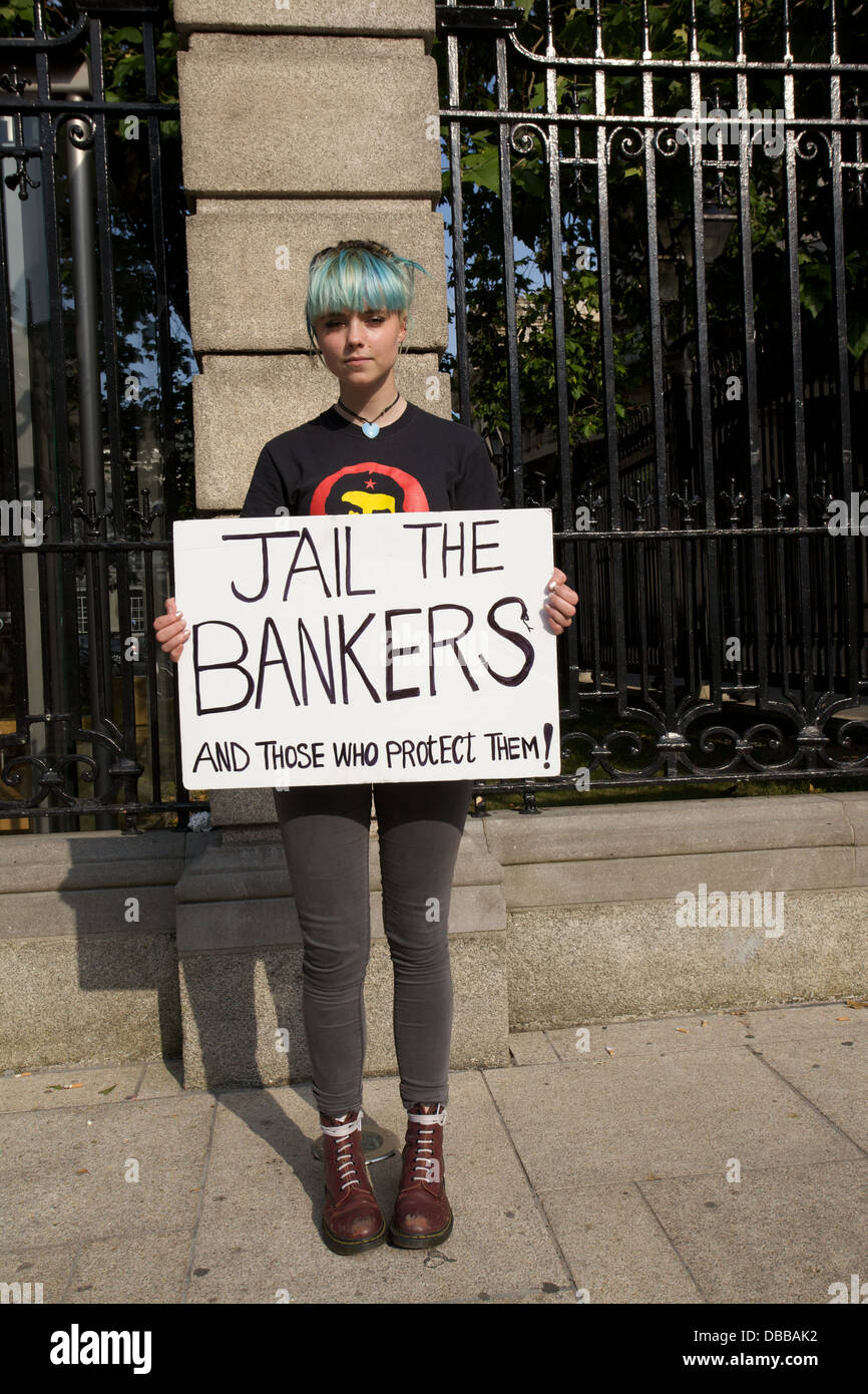 Portrait of young female standing in the street in Dublin, Ireland, with a protest placard reading Jail the Bankers - Stock Image
