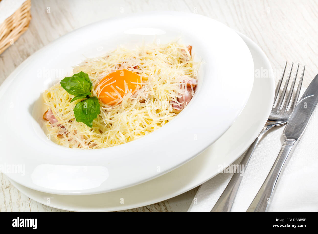 spaghetti with egg on a table in a restaurant - Stock Image