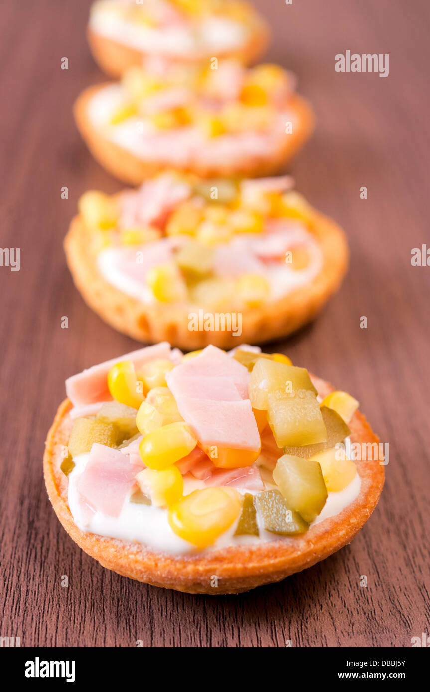 Small appetizers on the wooden table. Selective focus on the front cup - Stock Image
