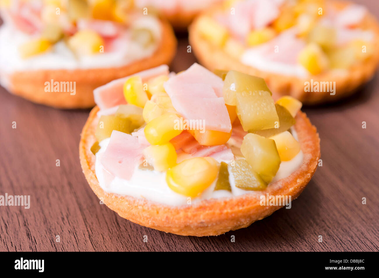 Small cups with ham and vegetables. Selective focus on the top ham - Stock Image