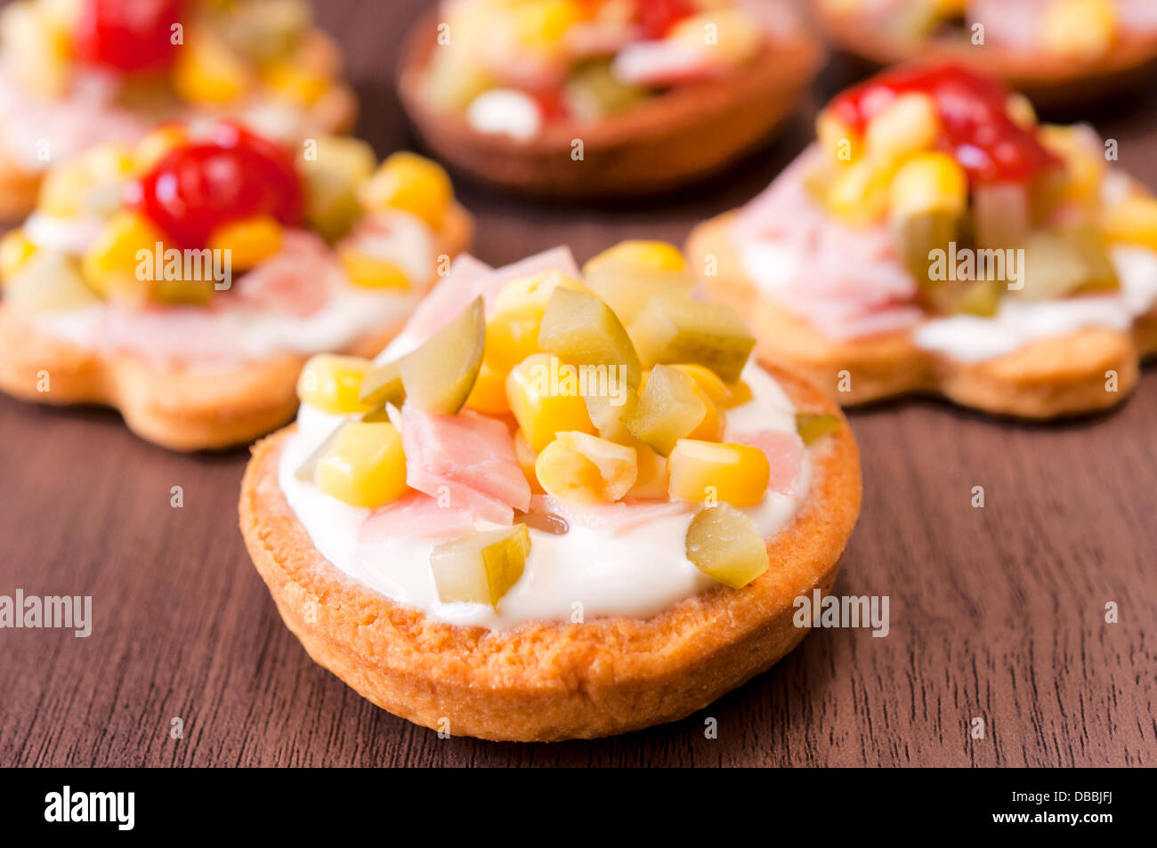 Appetizer filled with vegetables, ham and mayonnaise on wooden table - Stock Image