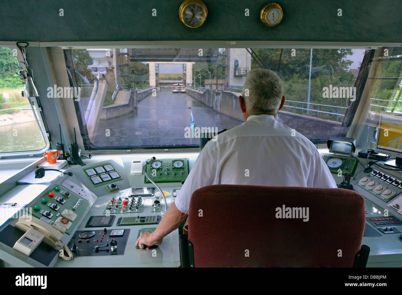 Captain at the controls of a modern Dutch tourist approaching Neerharen Lock on a sightseeing trip from Maastricht - Stock Image
