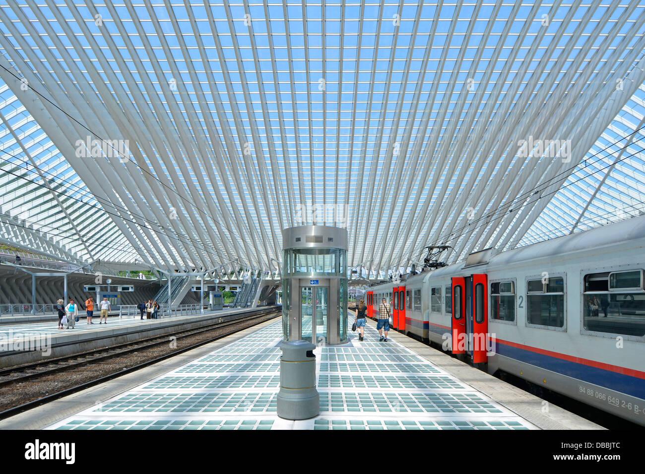 People on train platforms & couple walking away along  station platform Liège Belgium below modern building - Stock Image