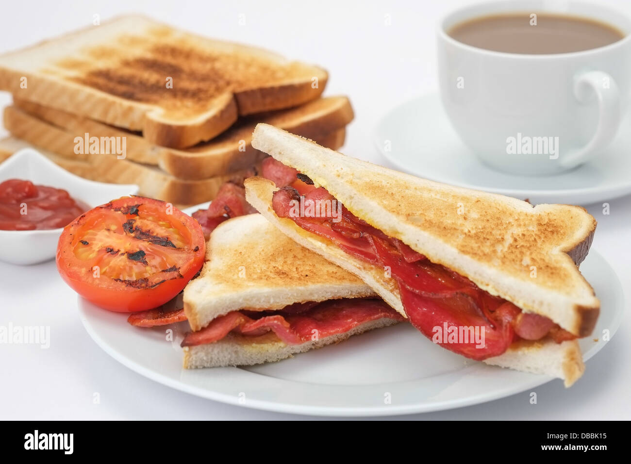 Breakfast of a bacon sandwich with toast and a cup of coffee - Stock Image