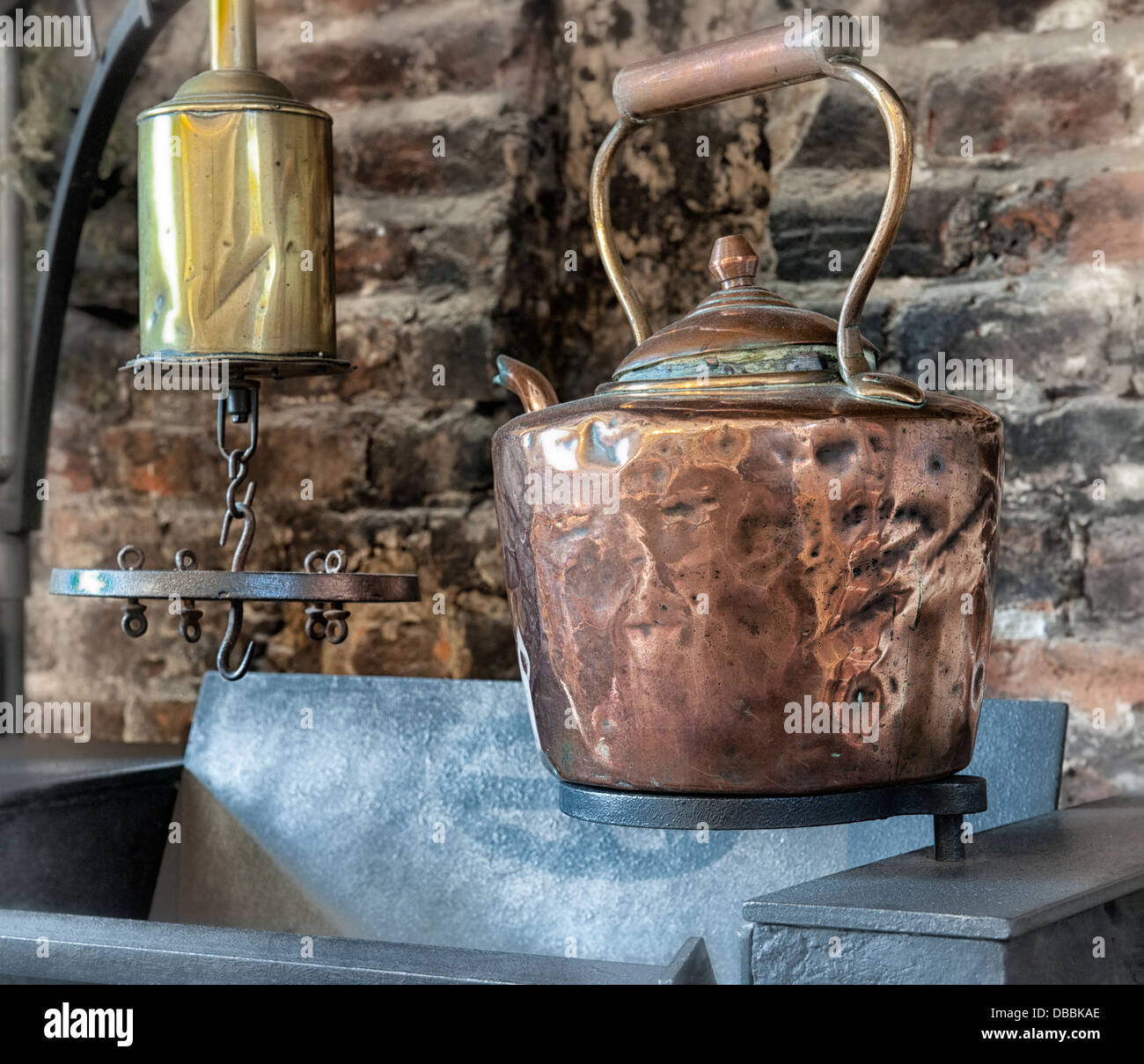 Copper kettle hanging above old stove. - Stock Image