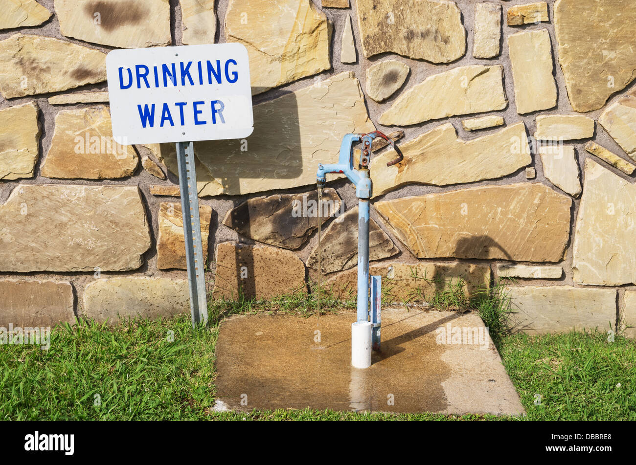 drinking water tap with sign and running water behind a stone wall - Stock Image