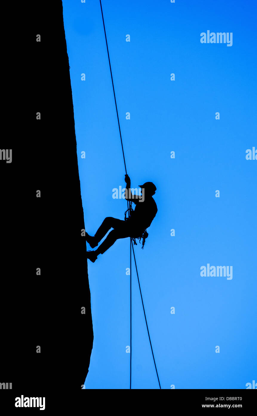silhouette of man rappelling down an overhanging cliff with blue sky background - Stock Image