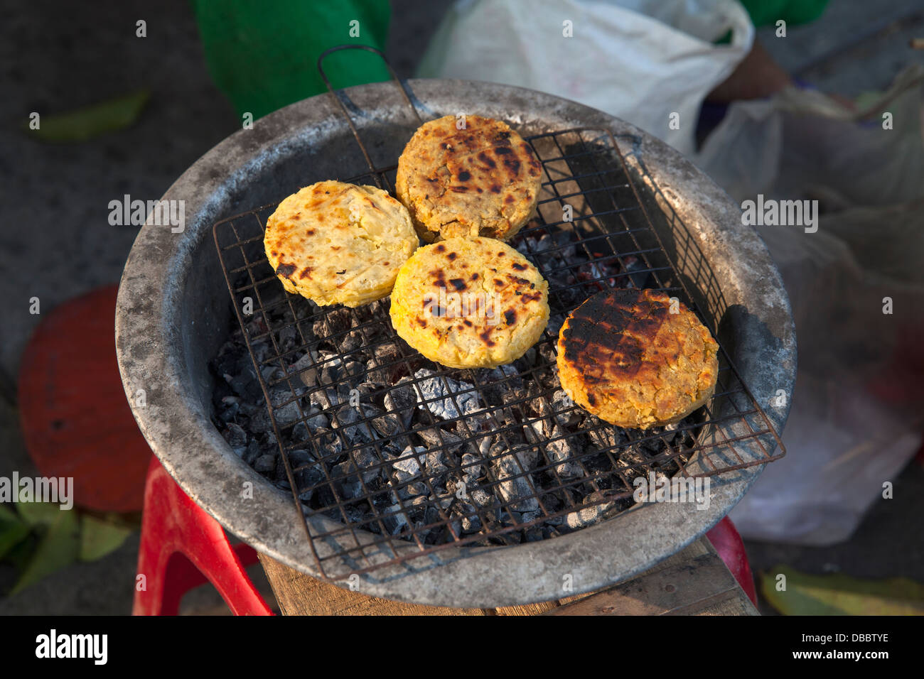 Sweet potato cakes grilling outside on street in Old Quarter, Hoi An, Quang Nam, Vietnam, Southeast Asia - Stock Image