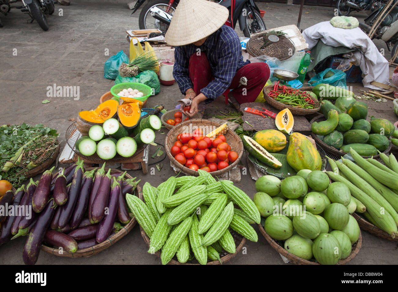 Woman selling fresh vegetables and other foods at market in Hoi An, Quang Nam, Vietnam, Southeast Asia - Stock Image