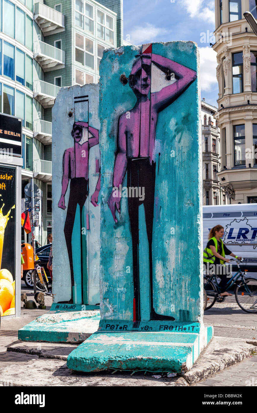 Paintings of men on colourful pieces of the Berlin wall at Checkpoint Charlie Border post, Friederichstrasse, Berlin Stock Photo