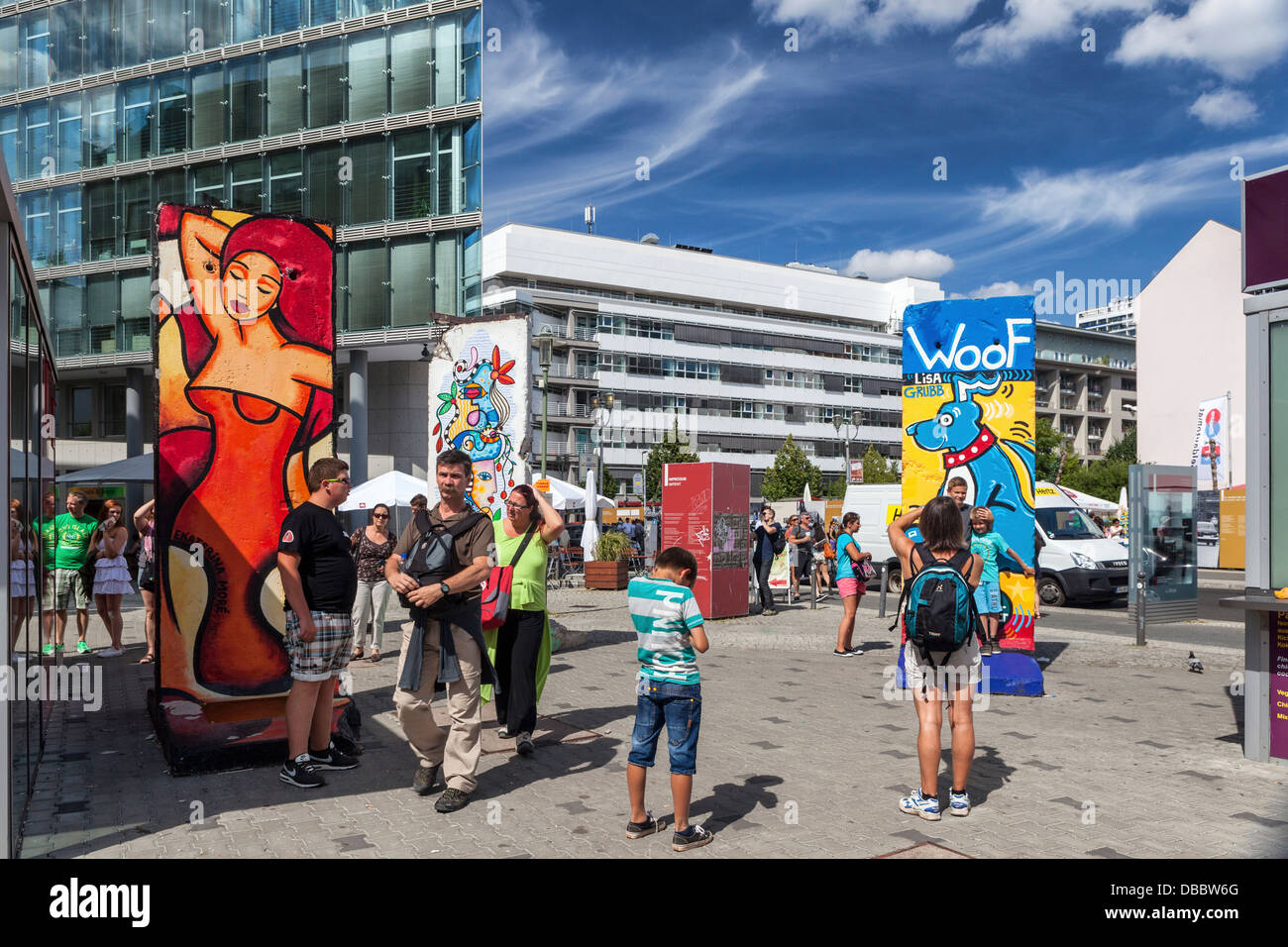 People, buildings and colourful pieces of the Berlin wall at Checkpoint Charlie Border post, Friederichstrasse, Stock Photo