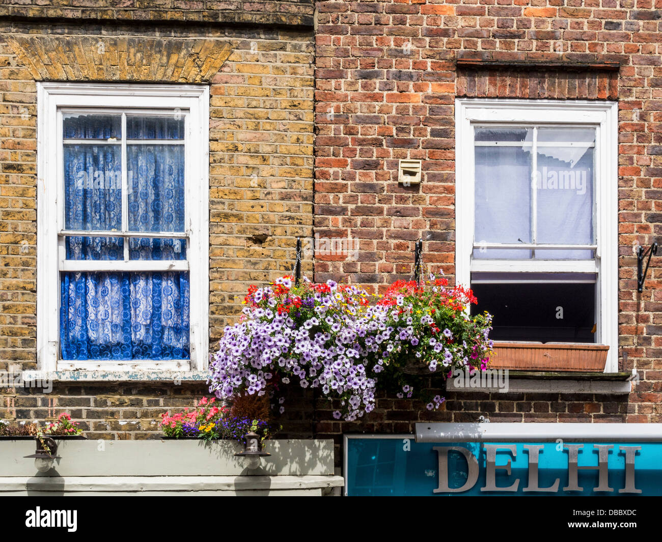 Window with blue net curtains and flower baskets above an Indian restaurant sign in Church Street. Twickenham - Stock Image
