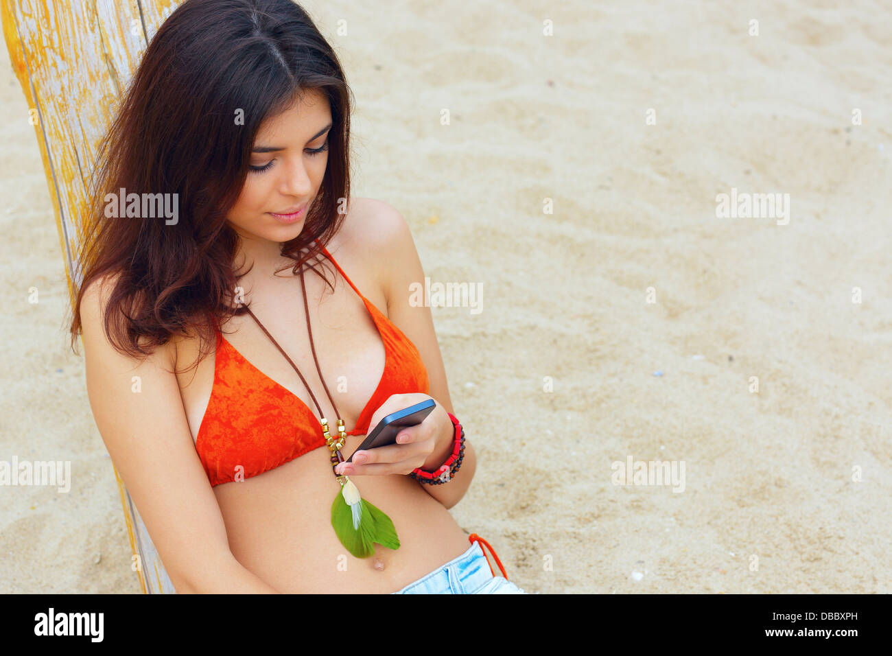 Young beautiful woman sitting on the beach with her smartphone - Stock Image