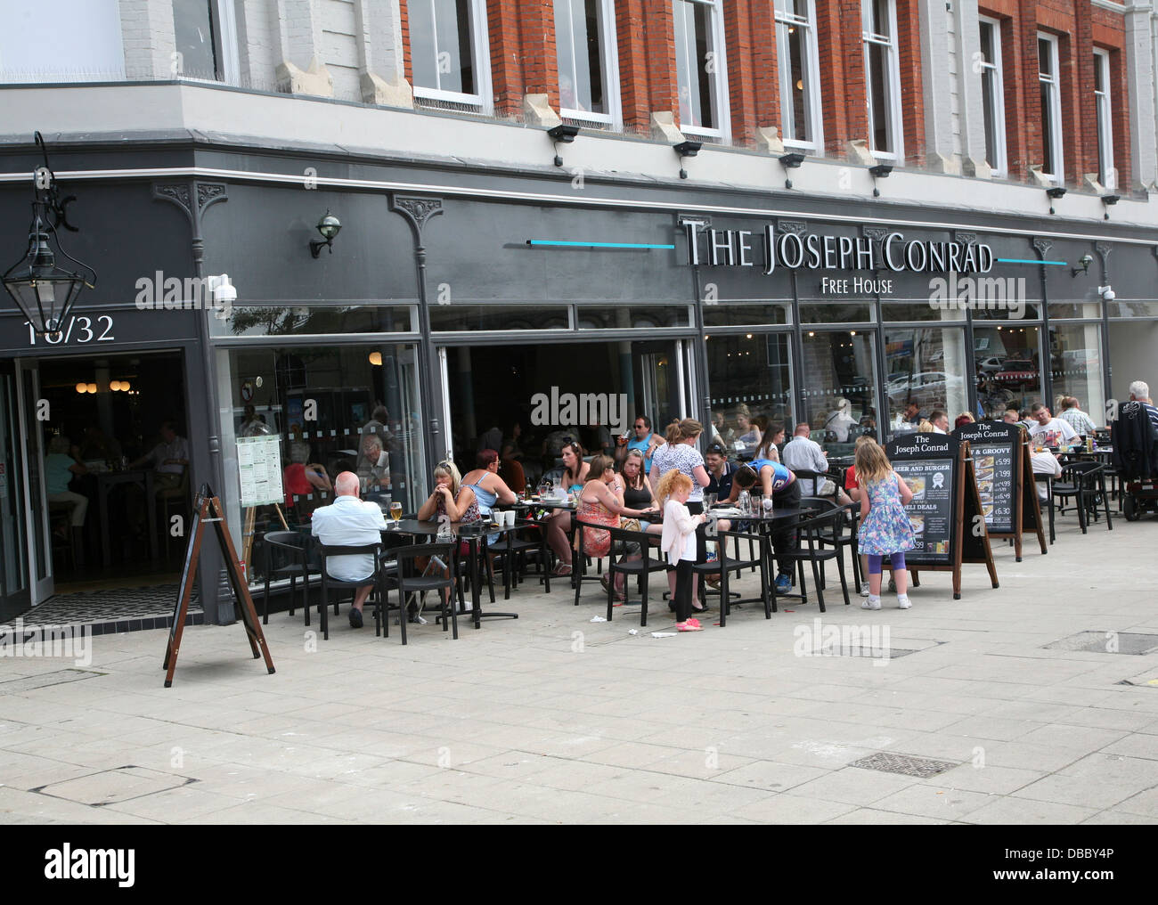 People sitting outside the Joseph Conrad wetherspoons pub Lowestoft Suffolk England in converted shop building - Stock Image