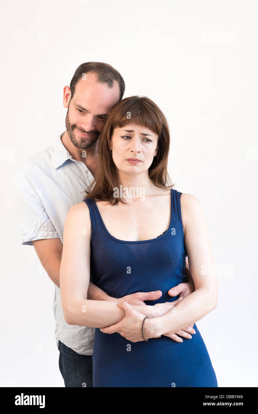 Young adult couple, happy man holding hugging woman from behind - Stock Image