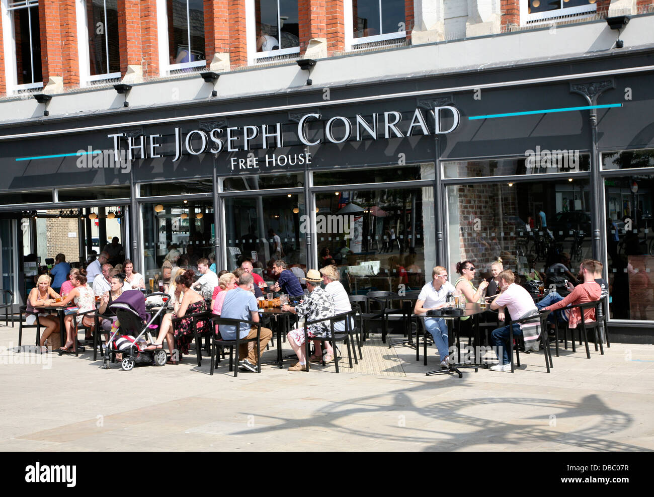 People sitting outside The Joseph Conrad Wetherspoons pub Lowestoft Suffolk England converted from former shop - Stock Image